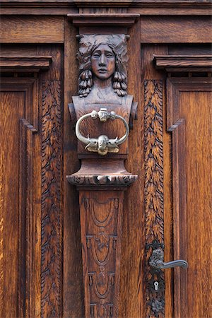 Close-up of door knocker on decorative, carved wood door, Cesky Krumlov, Czech Replublic. Stock Photo - Premium Royalty-Free, Code: 600-08232181
