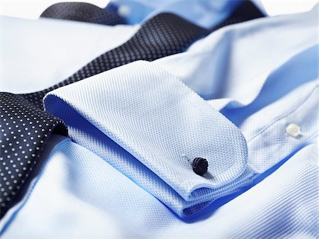 Detail of cuff of blue shirt with tie over in studio Stock Photo - Premium Royalty-Free, Code: 600-08312064