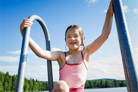 Young girl in swim suit climbing ladder out of lake, Sweden Stock Photo - Premium Royalty-Free, Code: 600-08353426