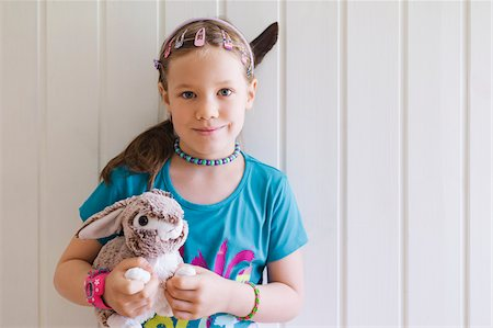 pretty - Portrait of young girl standing in front of wall holding her toy bunny, Sweden Stock Photo - Premium Royalty-Free, Code: 600-08353428