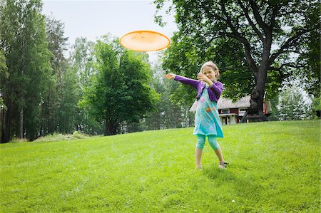 Young girl playing with a frisbee in the garden, Sweden Stock Photo - Premium Royalty-Free, Code: 600-08353429