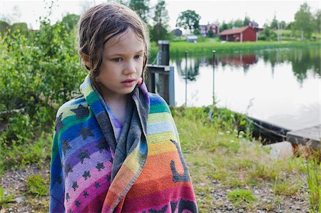 Portrait of girl standing on lakefront daydreaming and wrapped in beach towel, Sweden Stock Photo - Premium Royalty-Free, Code: 600-08353430