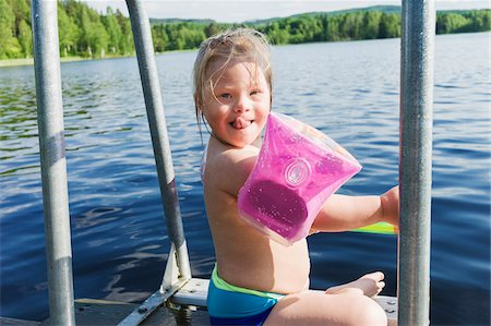 Girl with Down Syndrome wearing Water Wings Sitting on Jetty of Lake, Sweden Stock Photo - Premium Royalty-Free, Code: 600-08519474