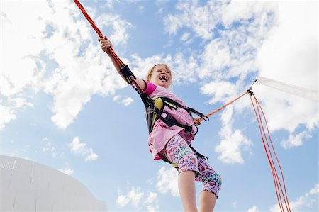 6 year old girl jumping with a bungee trampoline on a sunny day, Germany Stock Photo - Premium Royalty-Free, Code: 600-08512528