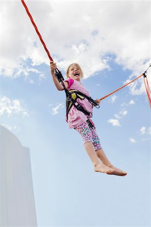 6 year old girl jumping with a bungee trampoline on a sunny day, Germany Stock Photo - Premium Royalty-Free, Code: 600-08512531
