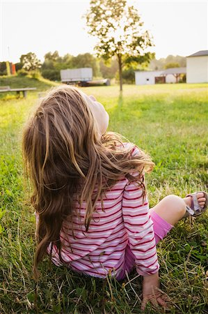 perception - 5 year old girl sitting on the grass on a sunny evening and staring at the sky, Germany Stock Photo - Premium Royalty-Free, Code: 600-08512533
