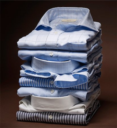 Stack of men's dress shirts on brown background Stock Photo - Premium Royalty-Free, Code: 600-08542911