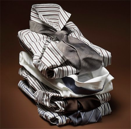 Stack of men's, striped dress shirts with ties on brown background Stock Photo - Premium Royalty-Free, Code: 600-08542912