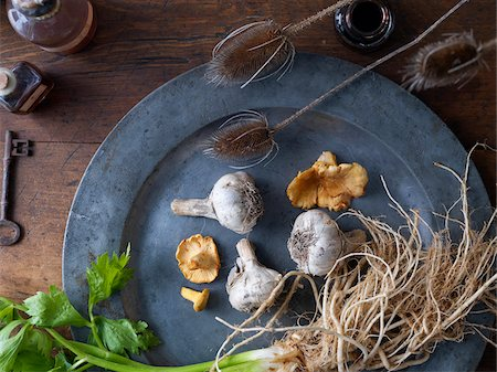 Overhead View of Pewter Plate with Wild Mushrooms, Garlic and Celery on Wooden Surface with Old Key, Bottles and Dried Bullrushes Photographie de stock - Premium Libres de Droits, Code: 600-08559845