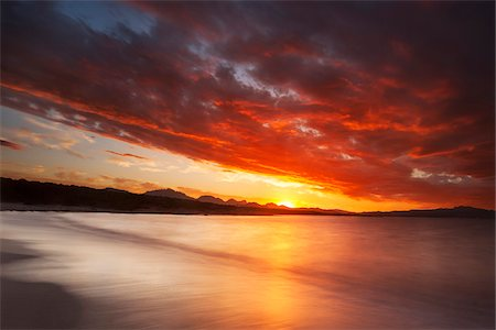 Dramatic red sunset at Cala Sabina Beach in Golfo Aranci in the Province of Sassari in Sardinia Stock Photo - Premium Royalty-Free, Code: 600-08765591