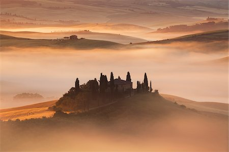 Overview of Podere Belvedere in a sunlit mist at sunrise at San Quirico D'Orcia in Val d'Orcia in Tuscany, Italy Stock Photo - Premium Royalty-Free, Code: 600-08765611