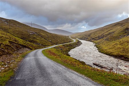 Winding road with river and cloudy sky in the highlands at Glen Coe in Scotland, United Kingdom Stock Photo - Premium Royalty-Free, Code: 600-08973451