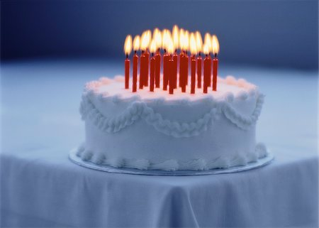 Cake with Lit Candles on Corner Of Table Stock Photo - Premium Royalty-Free, Code: 600-00057103
