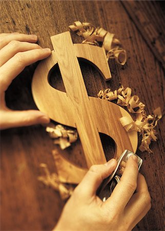 Close-Up of Hands Carving Wooden Dollar Sign Stock Photo - Premium Royalty-Free, Code: 600-00073204