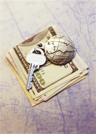 Key with Globe Keychain on Stack Of Currency on Map Stock Photo - Premium Royalty-Free, Code: 600-00073207
