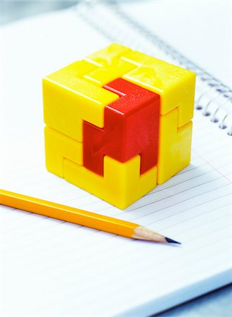education concept - Cube Puzzle and Pencil on Notebook Stock Photo - Premium Royalty-Free, Code: 600-00199211