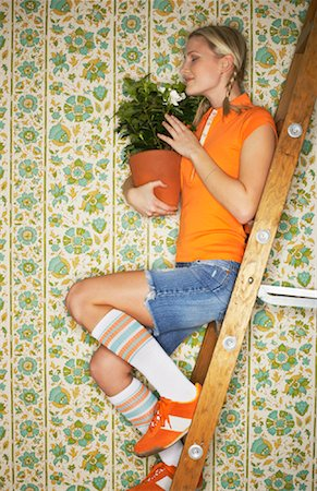 Woman Sitting on Ladder, Holding Plant Stock Photo - Premium Royalty-Free, Code: 600-00824482