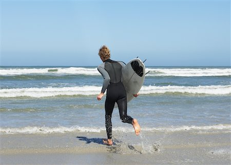 Surfer At The Beach Stock Photo - Premium Royalty-Free, Code: 600-00824625