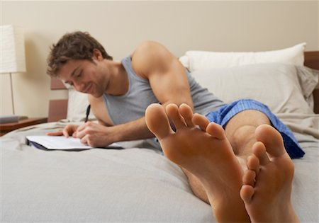 Man Writing on Bed Stock Photo - Premium Royalty-Free, Code: 600-00847762
