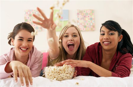 Girls Throwing Popcorn in Bedroom Stock Photo - Premium Royalty-Free, Code: 600-00847981