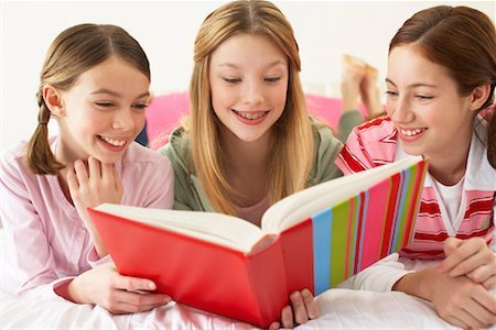 Girls Lying on Bed, Reading Book Stock Photo - Premium Royalty-Free, Code: 600-00866167