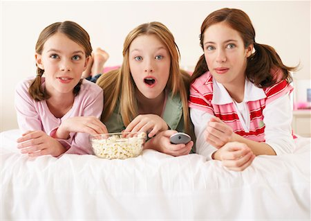 Girls Lying on Bed, Eating Popcorn Stock Photo - Premium Royalty-Free, Code: 600-00866168