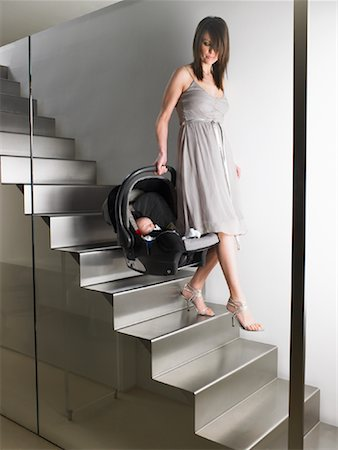 Woman Carrying Baby Seat down Stairs Stock Photo - Premium Royalty-Free, Code: 600-00917266
