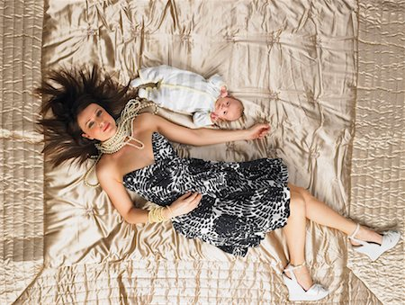 Woman Lying on Bed with Baby Stock Photo - Premium Royalty-Free, Code: 600-00917276