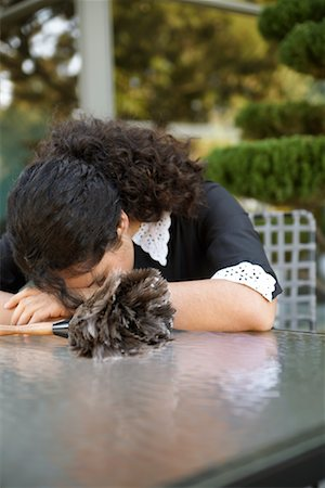 Maid Resting Head On Table Outdoors Stock Photo - Premium Royalty-Free, Code: 600-00917491