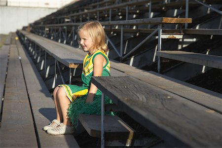 Girl Dressed as Cheerleader in Bleachers Stock Photo - Premium Royalty-Free, Code: 600-01015108