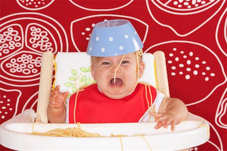 Baby in High Chair with Spaghetti Bowl on Head Stock Photo - Premium Royalty-Free, Code: 600-01015395