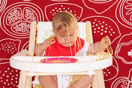 Baby with Spaghetti in High Chair Stock Photo - Premium Royalty-Free, Code: 600-01015393