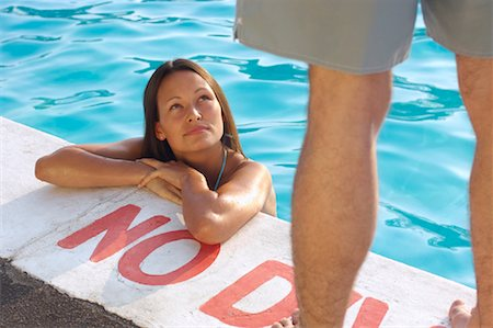 Woman in Swimming Pool Looking up at Man Stock Photo - Premium Royalty-Free, Code: 600-01041631