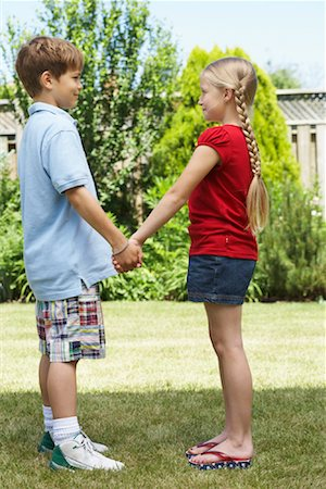 preteen thong - Sideview of Boy and Girl Standing in Backyard Holding Hands Stock Photo - Premium Royalty-Free, Code: 600-01042003