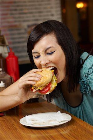 Woman Eating Hamburger Stock Photo - Premium Royalty-Free, Code: 600-01042090