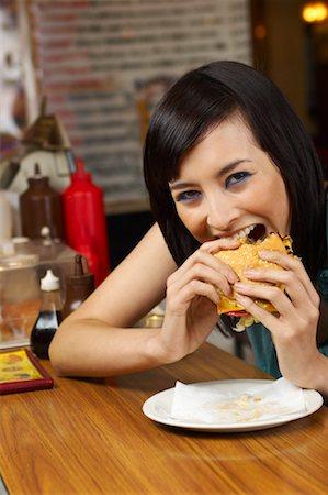 Woman Eating Hamburger Stock Photo - Premium Royalty-Free, Code: 600-01042091