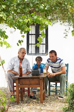 Grandfather, Father and Son Watching Television in Backyard Stock Photo - Premium Royalty-Free, Code: 600-01043369