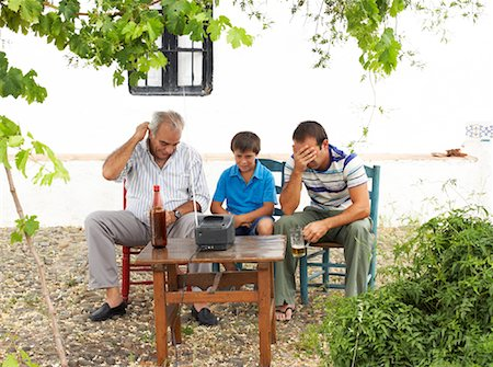 Grandfather, Father and Son Watching Television in Backyard Stock Photo - Premium Royalty-Free, Code: 600-01043375