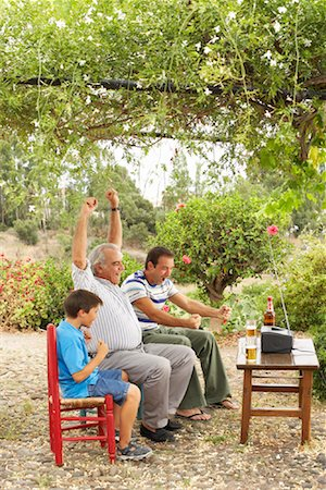 Grandfather, Father and Son Watching Television in Backyard Stock Photo - Premium Royalty-Free, Code: 600-01043376