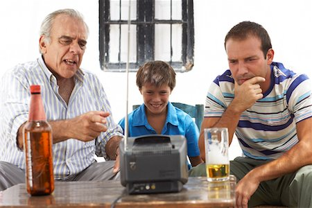 Grandfather, Father and Son Watching Television in Backyard Stock Photo - Premium Royalty-Free, Code: 600-01043370