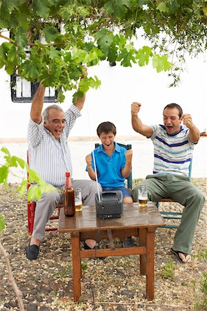 Grandfather, Father and Son Watching Television in Backyard Stock Photo - Premium Royalty-Free, Code: 600-01043373