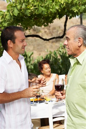 Father and Son Talking, with other Family Members in Background Stock Photo - Premium Royalty-Free, Code: 600-01043401