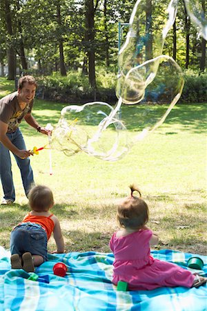 Father Blowing Bubbles while Babies Watch Stock Photo - Premium Royalty-Free, Code: 600-01073153
