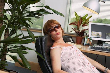 Woman Suntanning under Office Lamp Stock Photo - Premium Royalty-Free, Code: 600-01083307