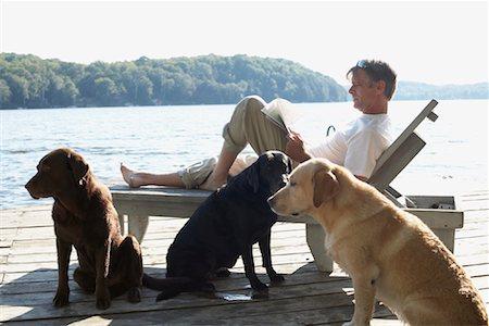 Man on Dock with Dogs, Three Mile Lake, Muskoka, Ontario, Canada Stock Photo - Premium Royalty-Free, Code: 600-01111416