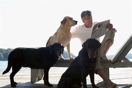 Man on Dock with Dogs, Three Mile Lake, Muskoka, Ontario, Canada Stock Photo - Premium Royalty-Free, Code: 600-01111417