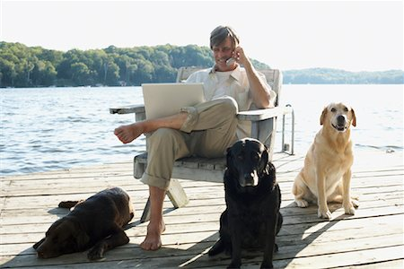 Man on Dock with Dogs, Three Mile Lake, Muskoka, Ontario, Canada Stock Photo - Premium Royalty-Free, Code: 600-01111428