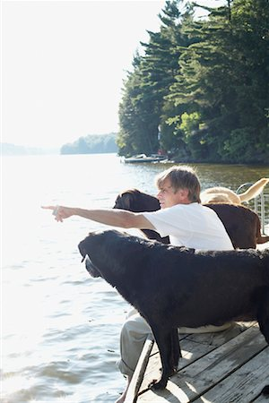 Man on Dock with Dogs, Three Mile Lake, Muskoka, Ontario, Canada Stock Photo - Premium Royalty-Free, Code: 600-01111423