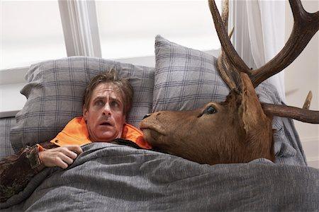 deer hunt - Hunter Sleeping with Deer Head Stock Photo - Premium Royalty-Free, Code: 600-01124363