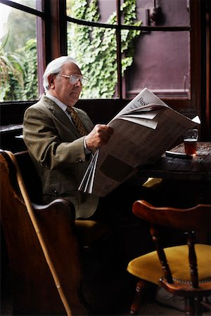Man Reading Newspaper in Pub Stock Photo - Premium Royalty-Free, Code: 600-01123736
